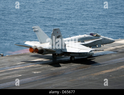 A US Navy F/A-18C Hornet launches from the flight deck of aircraft carrier USS Dwight D. Eisenhower April 9, 201 - Stock Photo