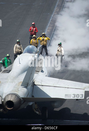 A US Navy plane director guides an F/A-18C Hornet onto a catapult for take off on the flight deck of aircraft carrier - Stock Photo