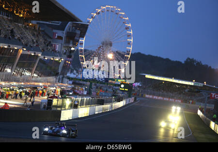 The cars are passing the start lane as night sets in during the 80th 24 Hours Race of Le Mans on the Circuit de - Stock Photo