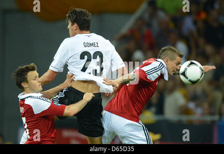 Germany'sMario Gomez (C) vies for the ball with Denmark's William Kvist and Daniel Agger (R) during the UEFA EURO - Stock Photo
