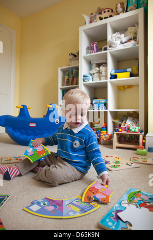 2 year old boy plays with various jigsaw puzzles in his bedroom, England, UK - Stock Photo