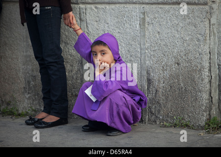A boy dressed as a penitent holds her mother hands during Easter Holy Week in Antigua Guatemala - Stock Photo