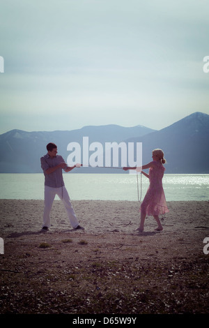a couple fighting and pulling a chain - Stock Photo