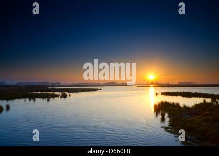 sun rising up over blue lake - Stock Photo