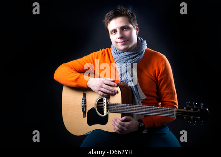 Man on background posing with guitar on knee - Stock Photo