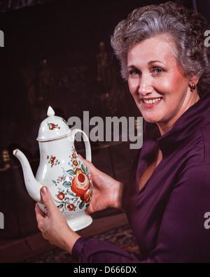 Woman with porcelain tea pot. - Stock Photo