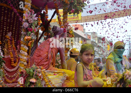 Little girl and hindu priest playing holi with rose petals - Stock Photo
