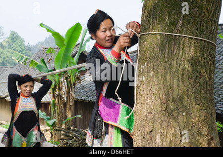 Women in the Congjiang Basha Miao Village prepare to strain their home-woven fabric - Stock Photo