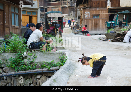 Funny Street Scene Zhaoxing village and river in the Guizhou province of China - Stock Photo