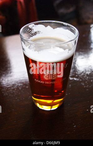 A printed pint glass of Batemans bitter on a bar pub table drinks glasses - Stock Photo