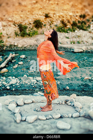 Woman outdoors near a river with her arms and heart open in a mandala of stones. - Stock Photo