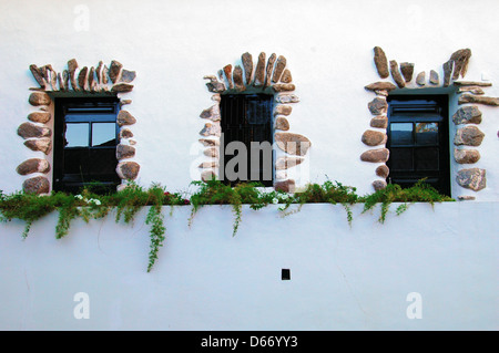Windows of an old house decorated with Basalt stones in Calda de Monchique a spa town in the Monchique Mountains - Stock Photo