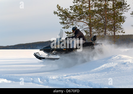 man riding a snowmobile on the lake - Stock Photo