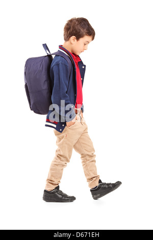 Full length portrait of a sad school boy walking, isolated on white background - Stock Photo