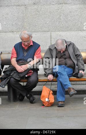 Trafalgar Square, London, UK. 14th April 2013. Two men dozing in the sunshine in Trafalgar Square. People enjoy - Stock Photo