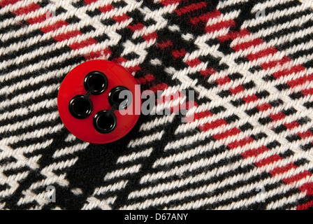 Plastic red button on a stylish checked fabric. - Stock Photo