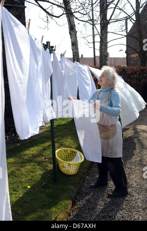 Elderly pensioner hanging out a line of washing on her washing line in April. - Stock Photo
