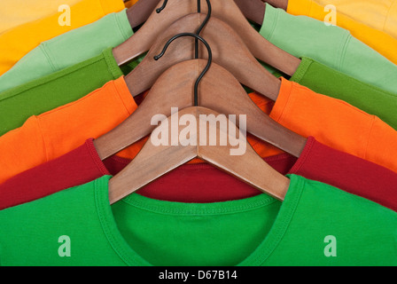 Choice of bright colorful t-shirts on wooden hangers. - Stock Photo