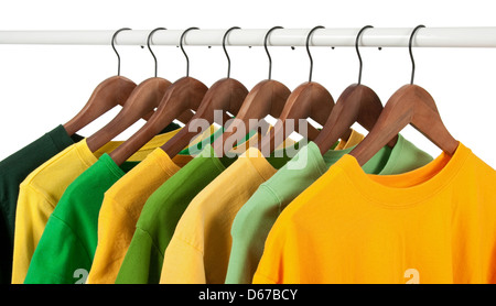 Choice of green and yellow shirts and t-shirts on wooden hangers, isolated on white. - Stock Photo