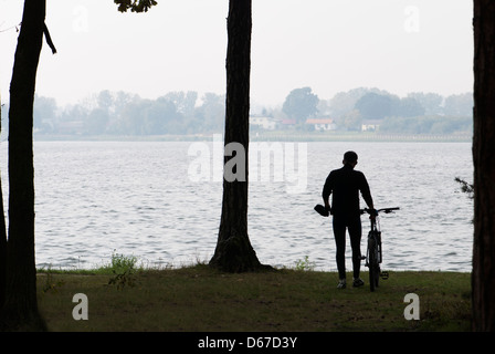 Silhouette of cyclist along the bank of Zemborzycki lake, Lublin, Poland, Europe - Stock Photo