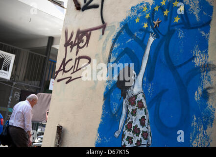 A man walks past a graffiti showing a girl reaching for the stars in Athens, Greece, 19 June 2012. Photo: Emily - Stock Photo