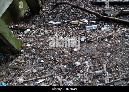 Detritus, broken pottery, glass and clay pipes on the riverbank foreshore of the River Thames at Queenhithe, City - Stock Photo