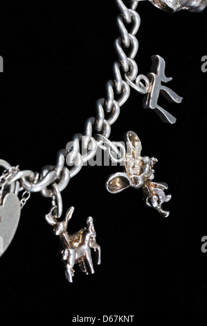 Sterling silver charm bracelet against a black background. - Stock Photo