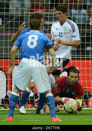 Italy's goal keeper Gianluigi Buffon (R) vies with Germany's Mario Gomez for the ball during the UEFA EURO 2012 - Stock Photo