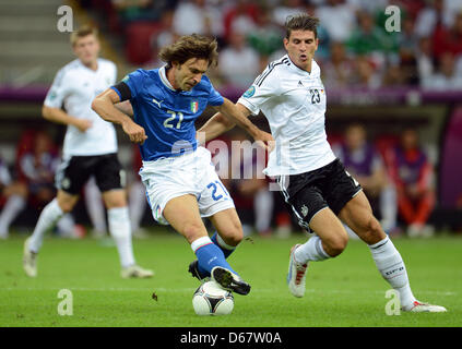 Germany's Mario Gomez (R) vies for the ball with Italy's Andrea Pirlo during the UEFA EURO 2012 semi-final soccer - Stock Photo