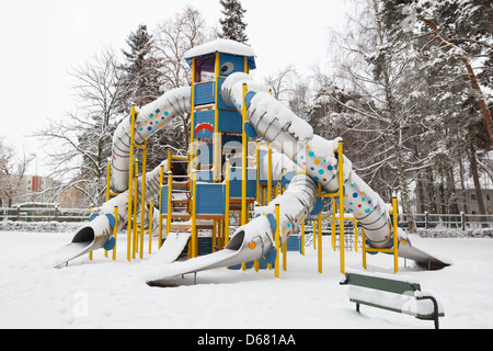 snowy slides in childrens playground park after the snow storm - Stock Photo