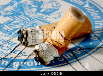 (dpa file)- A file picture dated 24 May 2008 shows cigarette buds lying on a beermat in Duesseldorf, Germany. The - Stock Photo