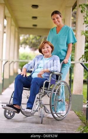in wheelchair with nurse in the garden of a nursing home stock photo