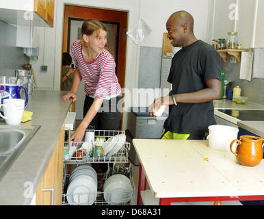 Abduorahmane Seck from Senegal and nursery worker Juliane Pfeffer work in the kitchen at Karl Schubert School, Free - Stock Photo