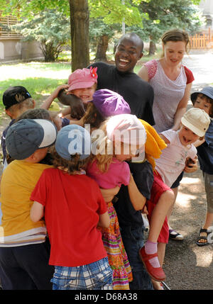 Abduorahmane Seck from Senegal and special education teacher Susanne Floegel exercise with first grade students - Stock Photo