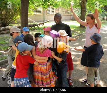Abduorahmane Seck (back) from Senegal and special education teacher Susanne Floegel (L) exercise with first grade - Stock Photo