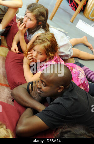 Abduorahmane Seck (bottom) from Senegal reads with first grade students at Karl Schubert School, Free Waldorf School, - Stock Photo