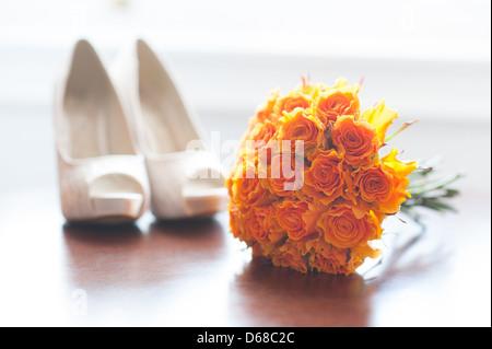wedding shoes and bouquet of orange roses nobody - Stock Photo