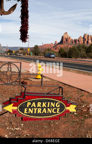 A parking entrance sign with a fire hydrant next to a road and red rocks in the background, Sedona, Arizona, USA - Stock Photo