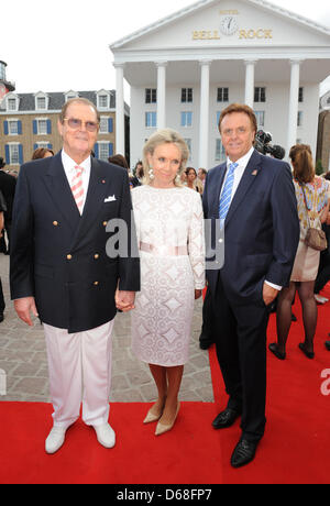 Managing director Roland Mach (R), British actor Sir Roger Moore and his wife Kristina Tholstrup pose for the photographers - Stock Photo