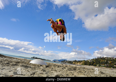 Young man somersaulting on the beach. Photographed in Nelson New Zealand. Model Re1lease Availanle - Stock Photo