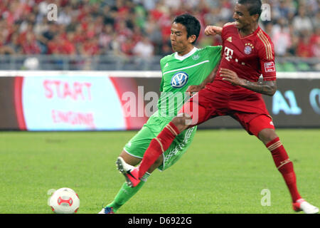 Wolfsburg's Makoto Hasebe (L)vies for the ball with Bayern Munich's Luiz Gustavo during the test match of the German - Stock Photo