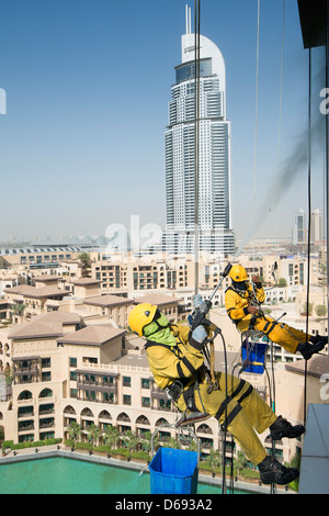 Window cleaners abseiling down high-rise apartment building in Dubai United Arab Emirates - Stock Photo