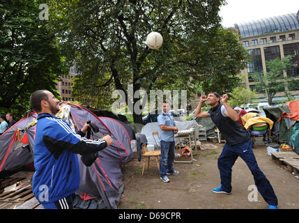 Two men practice headers with a soccer ball while the police clears the Occupy camp in Frankfurt am Main, Germany, - Stock Photo