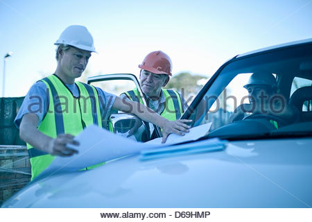 Construction workers reading blueprints - Stock Photo