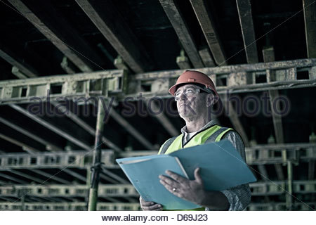 Construction worker reading blueprints - Stock Photo