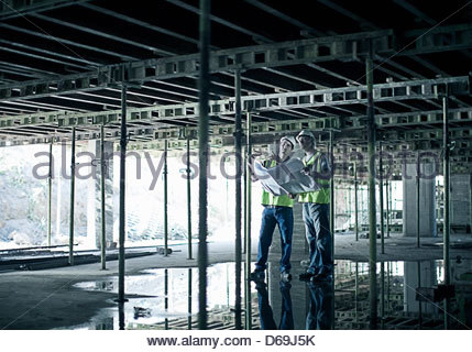 Construction workers using blueprints - Stock Photo