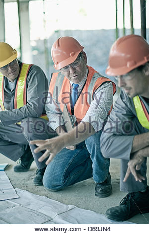 Workers and businessman on site - Stock Photo