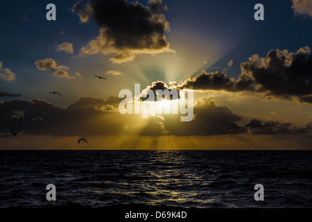 Sun breaking through clouds over water - Stock Photo
