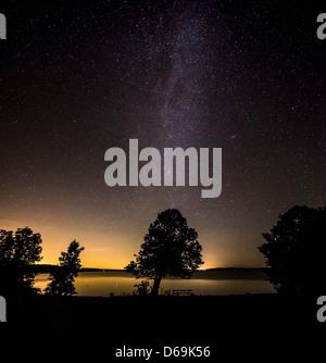 Illuminated night sky over rural landscape - Stock Photo