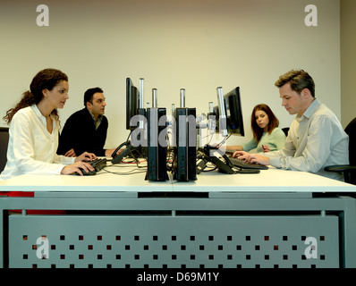 Business people using computers at desk - Stock Photo